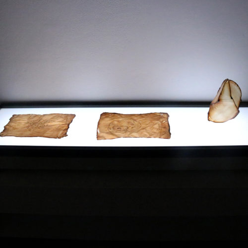 This is a color photograph of an installation and light projection by Maru Garcia. There are three objects placed on a table with a brightly lit top. The objects (left to right) are: a tan, flat drawing, another tan, flat drawing, and a sculpture that takes a biomorphic form. The sculpture is placed upright.