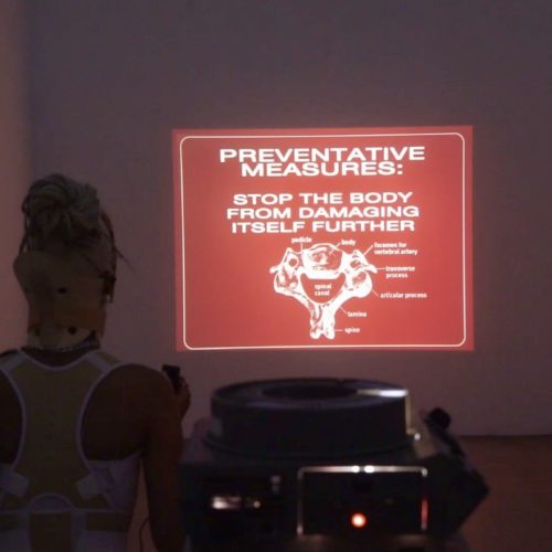This is a color still of a video work by Panteha Abareshi that features the artist with a 35mm slide projection in a dimly lit room. The artist faces the wall with the projection, which depicts a red and white rectangular graphic. The words in the graphic read (top to bottom, left to right): Preventative Measures, Stop the body from damaging itself further. Below these words is a diagram of a pelvis.