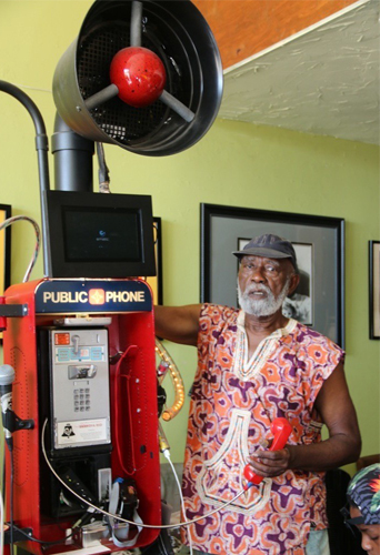 This photograph by Ben Caldwell features of an individual of color with white facial hair and wearing a grey cap and colorfully patterned sleeveless tunic. The individual holds a red wired telephone in their left hand while putting their right arm over and behind a large complicated structure containing impressions of a phone booth with the text Public Phone. Behind the individual and this structure are a few framed images hung onto the green wall.