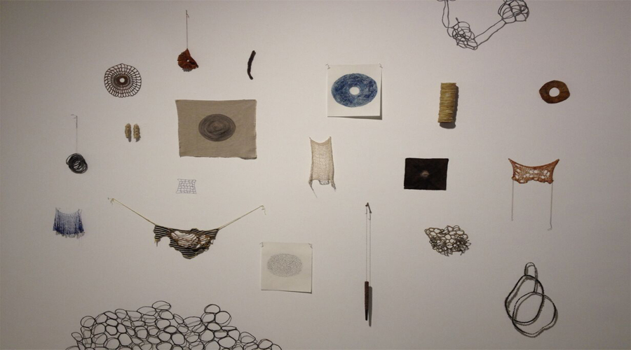 This installation view of the Fiberlicious exhibition includes artworks by Jennifer Reifsneider. Mounted onto the gallery wall, this collections of small and medium works involve the use of fibers and threading techniques to fabricate compositional objects. Seen here are a total of twenty-one artworks by the artist ranging in size, shape, and dimensionality.