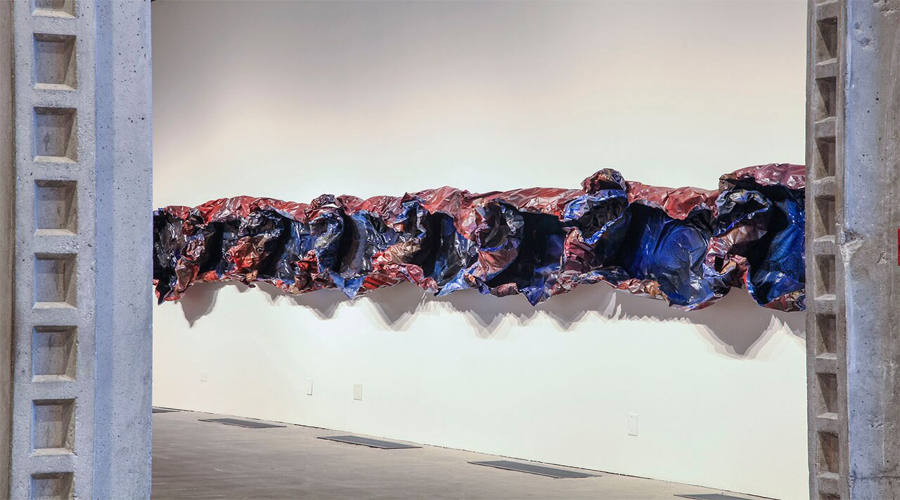 This sculpture by Sandeep Mukherhee spans horizontally across the wall and protrudes three-dimensionally into the exhibition space. The artwork consists of circular-like vessel forms, that have an impression of being crumbled or crinkled, conjoined side-by-side. The outer surface of the forms is of a desaturated red hue while the inner surface of the forms is a deeply saturated blue hue. The combination of color and physical manipulation of the material creates a highly textured presence highlighted by deep shadows created from the multitude of creases.