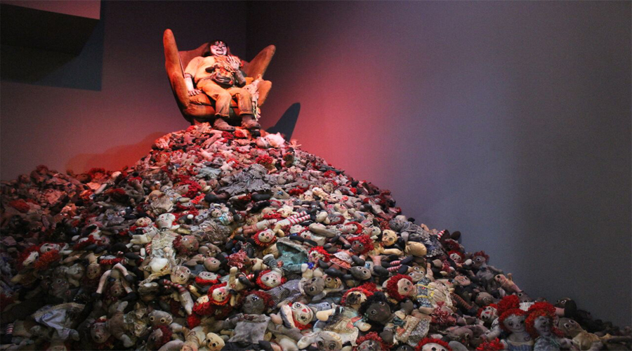 This artwork installation by the artist Marsian De Lellis consists of the impression of an individual, worn and deflated with a grotesque facial expression, sitting in a large chair. The individual in the chair is placed atop a very large ascending pile of children's dolls. The dolls are treated in a manner that renders them as worn, used, or allocative of time. The space in which the artwork is shown is illuminated with an ominous red that brings out the deep shadows of the various forms present to the viewer.