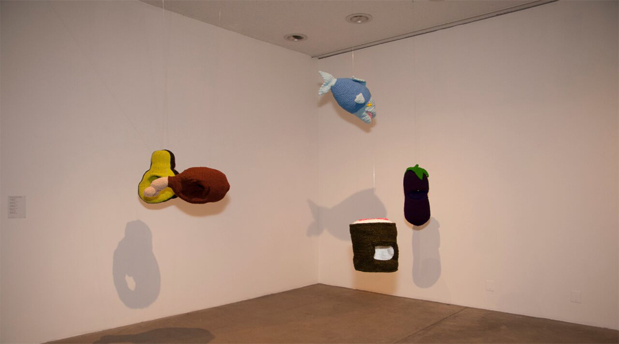 This installation view of the Fiberlicious exhibition includes artworks by Chili Philly also known as Phil Ferguson. Seen here are five fabricated and familiar objects suspended from the gallery ceiling towards a corner section of the exhibition space. The objects are rendered by the use of fabrics stitched together into a vessel-like sack. They are then stuffed and expose their three-dimensional familiar forms such as avocado, fish, and eggplant.
