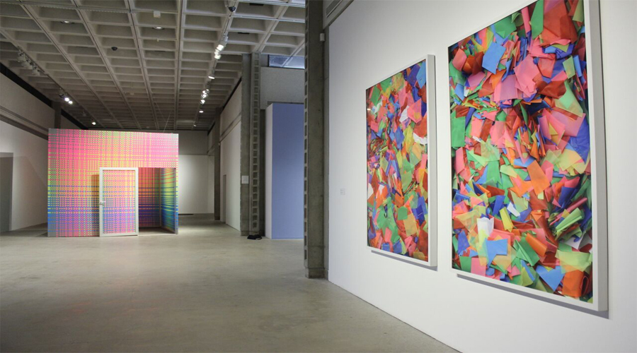 This installation shot of the COLA 2016 exhibition includes artworks by Megan Geckler. The artwork in the foreground is of two large works consisting of a multitude of colorful geometric shapes. The geometric shapes are arranged onto the surface of the artwork that resembles the techniques of collage. The combination of color tints, tones, and shades renders an allusion of three-dimensional space within the two-dimensional surface of the artwork. In the background of the installation image exists the other artwork by Megan Geckler which includes a large three-dimensional cubic room within the gallery space. Both the outside and inside of the form are treated with a highly saturated color grid-like pattern. The colors present resemble the colors utilized in the additionally included works. In the lower right portion of the form is a door, also treated with this colorful grid-like pattern and white trim, swung completely open revealing the inside of the form.