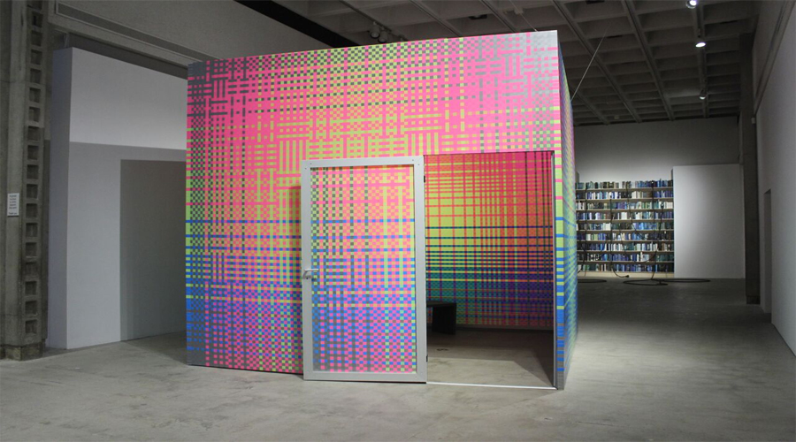 This installation image of the COLA 2016 exhibition includes artworks by Megan Geckler and Blue McRight. The artwork by Megan Geckler is in the foreground and includes a large cubic room residing within the exhibition space. The outer and inner sections of the form have been treated with a colorful grid-like pattern. On the front face of the artwork is a similarly treated door with white trim, swung wide open, revealing the interior of the large form. In the background is an artwork by Blue McRight in which a lit bookcase or book shelving has been inserted into the gallery wall. Tube-like forms extend from the spines of a few books and connect into sprinkler-like devices along the gallery floor.