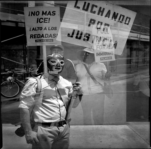 This photograph by the artist Leopoldo Peña features three individuals protesting and holding signs. The individaul in the foreground is wearing a luchador mask and holds a sign that says LUCHANDO POR JUSTICIA. The background individuals, seen here more translucent than the foregrounded individual, hold signs with the text: ¡No Mas ICE! ¡Alto A Los Redadas! and Full Rights For All Immigrants.