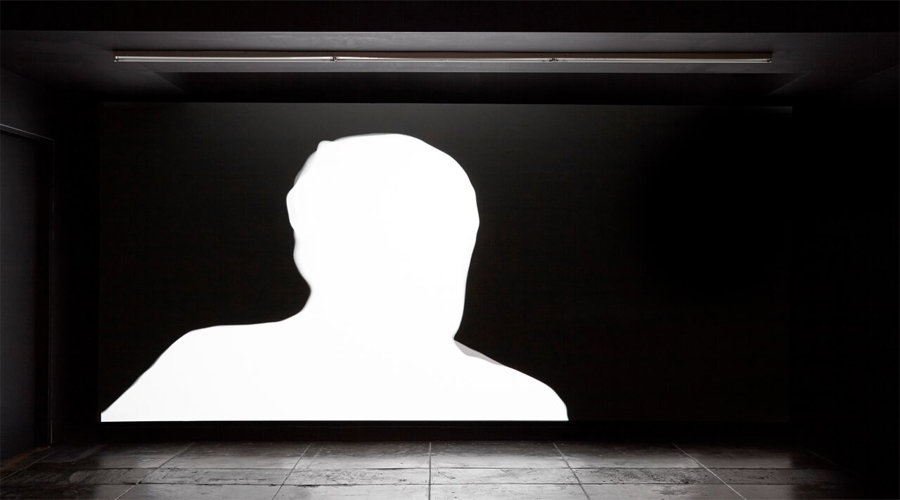 In this video installation by the artist Marco Kane Braunschweiler, the still features a large white silhouette of an individual's head and shoulders set agains a black background.