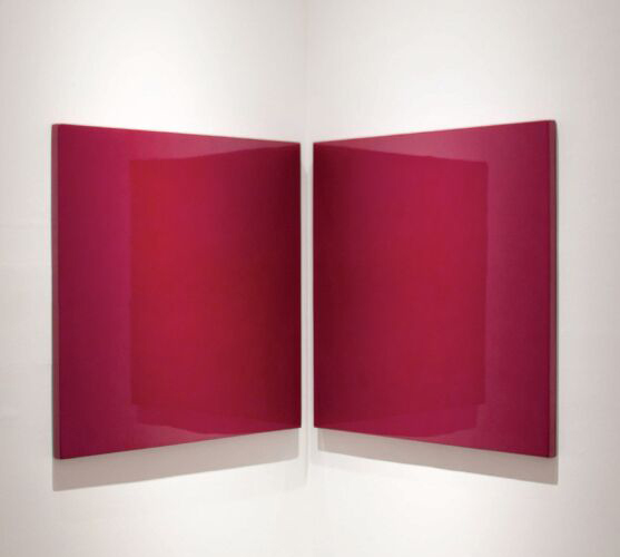 This sculpture by the artist Rubén Ortiz Torres shows two identical square panels made from semi-translucent-reflective urethane resin tinted red. These panels have been mounted in a side-by-side position on a corner portion of the gallery walls.