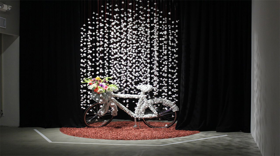This sculptural installation by Keiko Fukazawa depicts a bicycle that has had its armature or structural portion covered in white flower petals. The bicycle also contains a front-bar basket in which a colorful arrangement of flowers has been inserted into. The bicycle remains posed, upright, by its kickstand atop a bed of red flower petals. Linear red strands that have been threaded through more white flower pedals are draped behind the bicycle similar to a veil.