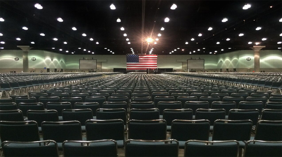 This artwork by Timothy Durant shows a large print of an auditorium or large public conference space. The floor space is filled with connected and side-by-side sitting grey chairs. Along the ceiling are rows of lights illuminating the space. At the center of the background of this artwork is a large American flag suspended tautly from the ceiling.