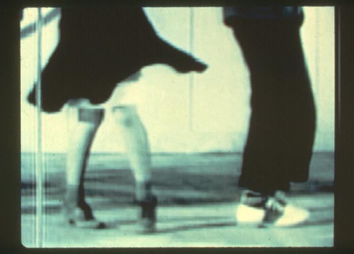 This video still of the installation by Bruce and Norman Yonemoto shows a black and white image of the bottom halves of two individuals. On the left is an individual wearing a flowing knee-length black dress, semi-translucent knee-high stockings, and lightly toned dancing boots. The legs seen here are bent inward and slanted slighty gesturing acts of dancing. On the right of the image is an individual wearing ankle-length black pants, angularly patterned socks, and white dress shoes containing a black diagonal stripe along the outter sides of the shoe. This individual is faced away from the other, knees bent forward, also gesturing dancing.