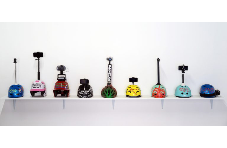 This sculptural installation by the artist James Berson includes a collection of nine helmets that have been altered by the attachment of a recording device. The helmets range in various colors and styles including bicycle, baseball, skateboard, etc. The nine helmets are also treated with applied text vinyl reading, Peaceful Protest Helmet. The nine helmets sit on a shelf mounted onto the gallery wall facing towards the gallery space.