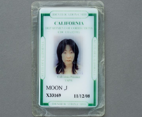 This artwork by Jennifer Moon shows a small framed and laminated I.D. card from the California Department of Corrections. The card contains an individual with medium length black hair and an emotionless facial expression along with text and numbers representative of the individual depicted here. The card is white with green accents and green and black text, it rests against a grey background.