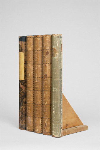 This scultpure by the artist Kim Schoen includes the spines of five bound books propped up by an attached wooden fabrication. The spines are worn and withered and range in colors of black, browns and green.