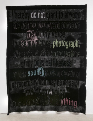 This artwork by the artist Mara Lonner shows a large, upright, rectangular black fabric containing the text, I hereby do not grant anyone the right to photograph or record me or my voice, to see my picture, photograph, silhouett, or the reproductions of my physical likeness or any soundtrack recording or records which may be made of me or my voice in connection to anything. Most of the words are in a black color, while the words do not, me, photograph, sound and anything are in various shades of ligher colors, such as pink, green and blue.