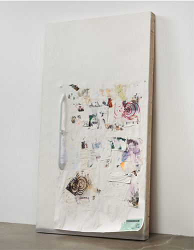 This sculpture by the artist Olga Koumoundouros is a large, rectangular white refrigerator door leaned back against the gallery wall in a vertical position. The surface of the refrigerator door is painted white, and has a textured surface containing various sized and colored drawings and photos. Some of the photos and drawings are peeling up. There is also a white, elongated handle for the sculpture (similar to an actual refrigerator door).