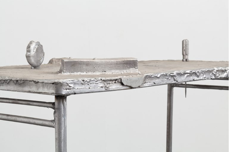 This sculpture by the artist Nick Kramer depicts a silver, metallic table containing several objects integrated on its surface. The objects on the table top include a thick disc-like form with circular grooves, a prismatic form, and a screwdriver pierced through the tabletop.