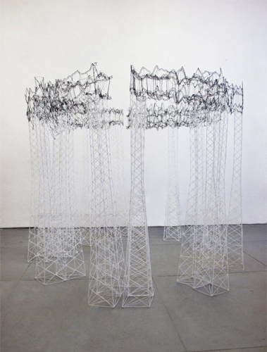 This sculpture by the artist Katie Grinnan is circular and stands upright. There are various scaffold-like support columns that form the base, and a ring-like form on top and a slight opening in between the center of the ring-like portion. Both the top and bottom portions of the sculpture are comprised and weaved using various strands of metal in different shades of silver (from light to dark).