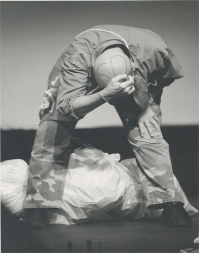 In this black and white still of a performance by the artist Rachel Rosenthal, the artist is wearing camouflage print apparel bent forward and downward. She is clenching the top of her head with her right hand whilst standing over a bundled pile of plastic material. In the background, a blurred imagery of Mojave Desert landscape is shown.