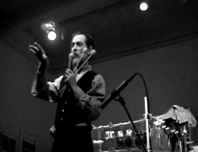 In this still of a performance by the artist Ron George, the artist is seen holding a pair of percussion instrument sticks and speaking into a microphone in the same hand while gesturing towards an assumed audience with the other hand. Beside the individual is a stand for the microphone. In the background, more indications of another percussion instrument and lighting pointed down at the individual and their performance space.