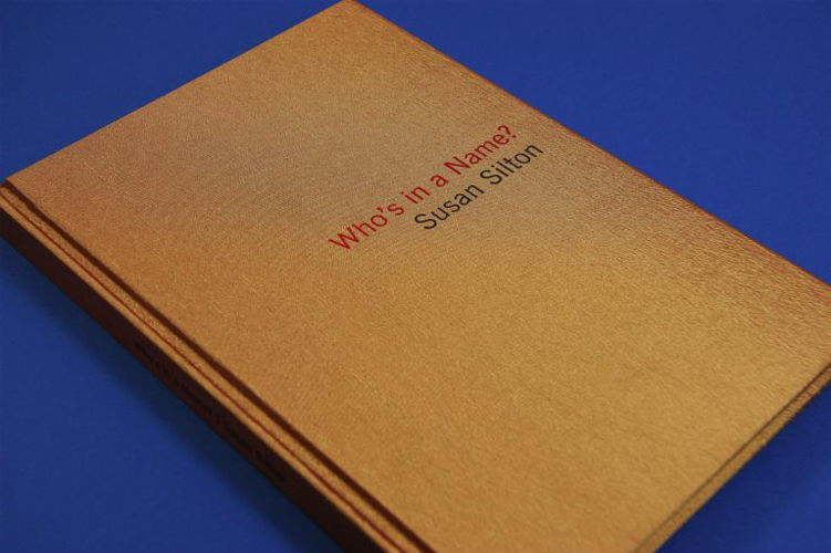This artwork by the artist Susan Silton depicts the front cover of a tan bound book with red text that reads Who's in a Name? and black text that says Susan Silton. The book lays flat and angled against a deep blue background surface.