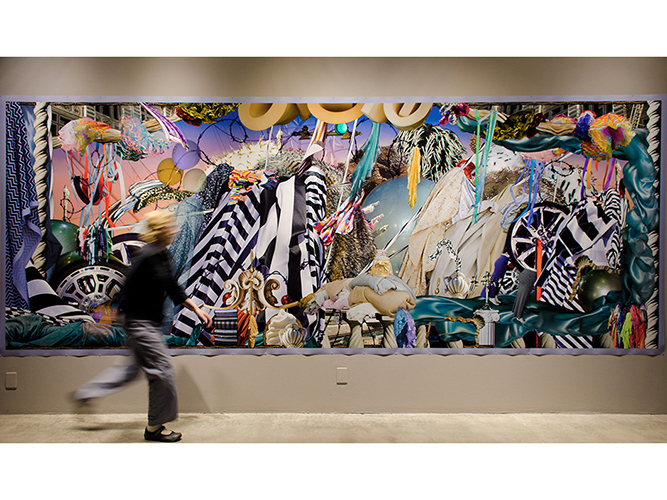 This large scale photographic print by Barbara Strasen presents a collage-like render of forms, figures, objects, lines, and more. The piece is overwhelmingly energized with notions of movement, activity, and color. Some familiar imagery depicted here is tires or wheels, architectural columns and classical plinths, fabrics, and the impressions of cityscapes. In front of the image is an individual, physically blurred by the engagement of motion. walking in form the left edge of the image and towards the right.