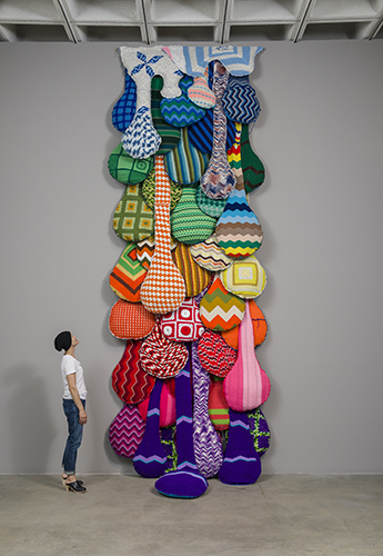 This sculpture by Miyoshi Barosh is a large-scale, fiber-based work consisting of a collage of large bulbous forms engaged in a suggested downward movement and leaving a strand or trail behind along the wall. The surface treatment of the artwork is a multi-layered attachment of these forms. Most forms visible here are uniquely designed with pattern-like shapes, lines, grids, colors, and more. The overall color scheme present is that of a traditional rainbow, utilizing tints, tones, and shades of these colors. The artwork also exists on the wall plane but reaches down and out onto the floor plane and into the exhibition space.