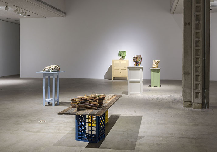 This installation view of the COLA 2015 exhibition features five artworks by Jeff Colson. There is one in the foreground, three in the middle ground, and one in the background. The foreground artwork includes a table-like structure fabricated by the use of two general-purpose utility crates, one yellow and one blue, and a large sheet of conjoined wooden planks. Resting atop the sheet is a dense pile of wood chunks. In the middle ground, from left to right, is a tall entry table that has been treated with an opaque light blue pigment. Atop the surface is a pile of wood chunks adhered together. The manner in which they adhere provides parts of the form to protrude out and onto the surface and therefore elevating the piece. To the right is a plinth-like furniture object treated with an opaque white pigment upholding a dense mass of adhered wood chunks. The wood chunks in this piece have been treated with colorful but opaque and highly desaturated pigments. The last artwork in the midground includes a shorter plinth-like furniture piece treated with an opaque pastel green pigment. Atop the surface of this artwork is an opaque yellow or tan form made of adhered wood chunks. The artwork in the background includes a larger cabinet-like furniture piece upholding a much more cubic form of wood chunks. The chunks have been treated with a multitude of mostly darker green pigments altered in their tints, tones, and shades. This form contains four fragile and small protrusions at the bottom that elevate it above the surface it stands on.