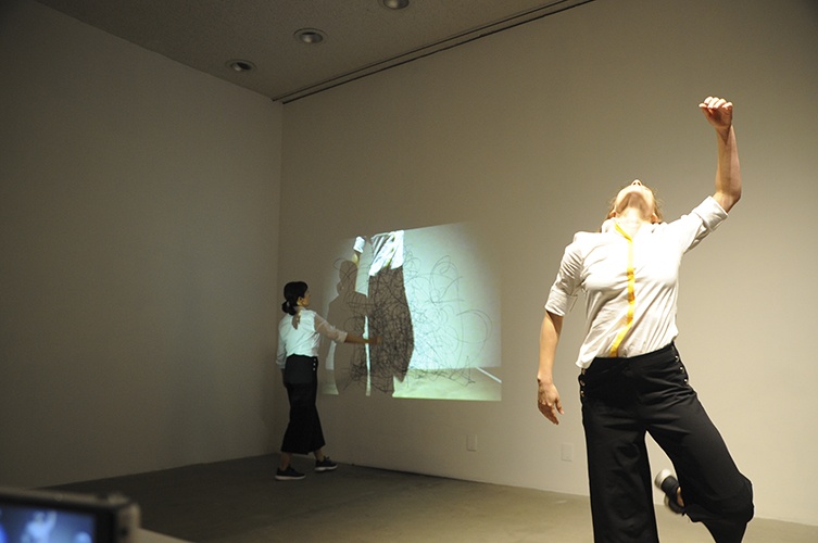This artwork by Elizabeth Leister shows a documented capture of the performance artwork. In this image, two individuals are present, one in the background gestured towards a gallery wall and video projection and the other gestured towards the viewer. The background individual faces the rear gallery wall in a walking motion. The individual raises their arm up and out towards the projection. The projection itself is a render of the individual in the foreground. Captured and reshown by a camera, not in view, the video projection in the background is a mirror image of the actions and movements engaged by the foregrounded individual. The foregrounded individual stands on one foot and their left arm raised. Spine arched backward, their head is tilted up and back to the gallery ceiling and lights above while their left leg is raised and bent at the knee.
