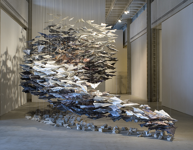 This sculptural installation by Joyce Dallal includes a large quantity of individual sheets of paper from varying sources with Japanese texts printed onto them. The individual sheets are folded into forms familiarly resembling common paper airplanes. Each individual plane is suspended within the exhibition space by visible threads latched to the gallery ceiling. The cluster of planes forms a large spacial mass that both gestures a downward swooping motion in its directional composition and physically engages in movement through its suspension and lightness in weight. Below the large mass are individual chunks of concrete curated into a form resembling a shadow cast by the large suspended mass. The individual threads weave through the individual planes and attach onto their individual concrete chunks.