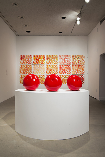 This installation view of the COLA 2014 exhibition includes artworks by Jessica Rath. In the foreground is a large sculptural work consisting of three spherical forms presented side-by-side. The spherical forms have been treated with a highly saturated red hue seen here reflecting light spots from the ceiling lights of the gallery. The three forms rest atop a large white curved plinth. In the background is a series of fifteen artworks mounted onto the gallery wall. Each rectangular panel is treated with an energized rendition of movements in applique and utilizes reds, yellows, and oranges. The panels are displayed in a grid-like manner consisting of three rows and five columns.