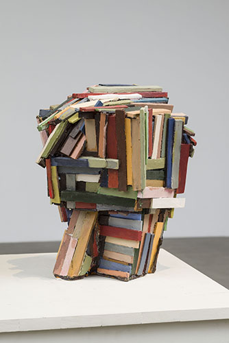 This sculpture by Jeff Colson is a medium-sized, wood-based consisting of a multitude of rectangular shapes that have been adhered together and treated with paint. The pigments seen here are colorful but rendered very opaquely and desaturated.