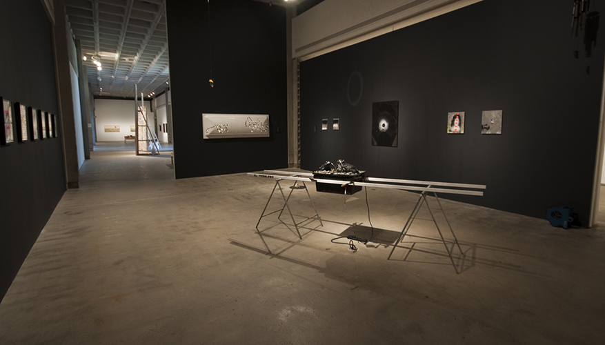 This installation image of the COLA 2012 exhibition features twelve visible wall-works and one large sculpture. The wall-works on the left gallery wall are mounted side-by-side. The artwork on the background wall is a large landscape-oriented image toned grey in pigment. Along the right wall are six more wall-works. From left to right: two small grey images mounted side-by-side, one large black image with a white circle in the center resembling an eye-like form, and finally two more small works side-by-side one grey and the other colorful and gesturing a render as a portrait. Within the space here is the sculptural work consisting of a make-shift table suspending a crate-like object filled with a black mass.