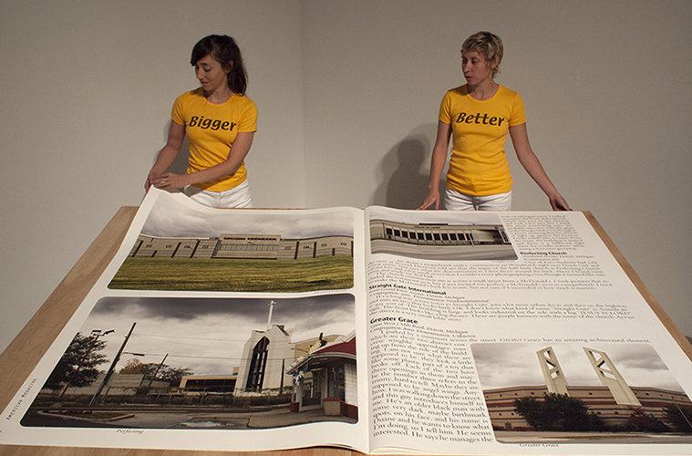 This artwork by Lisa Anne Auerbach features a large booklet opened and displaying text and images included within the booklet. The images shown include architectural buildings and structures. In the foreground, two individuals are seen here engaging with the booklet by turning the pages together. Both individuals are wearing yellow shirts with the text: Bigger (left) and Better (right).