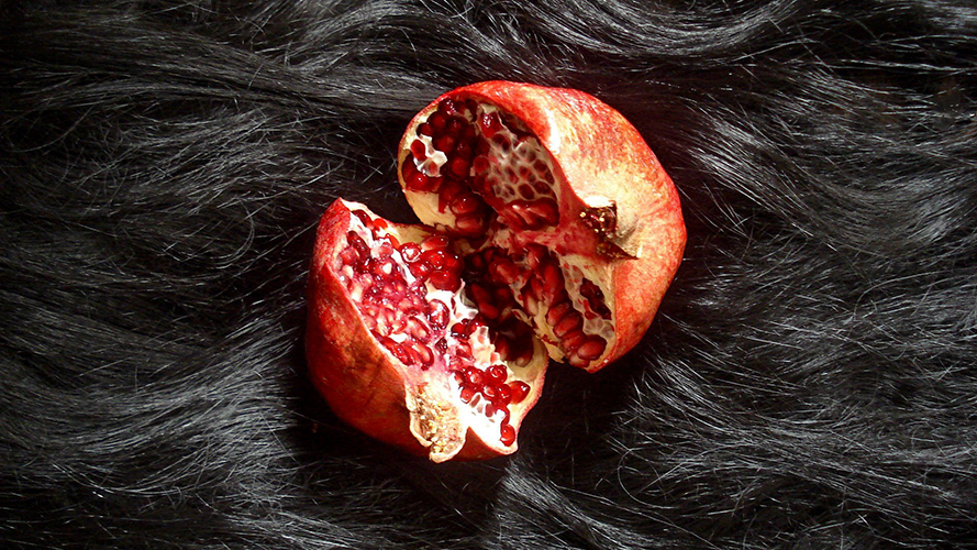 This photograph by Rika Ohara features an aerial shot depicting a pomegranate fruit severed in half. The severed fruit rests on top of a dense bed of long black hair.