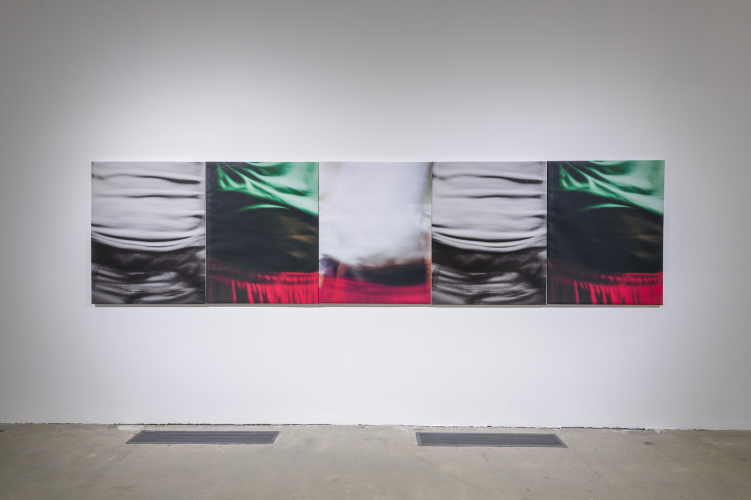 This is an artwork installation by the artist David Alekhuogie featuring five photographs printed on canvas. Each of these photographs depict slightly different angles of figures wearing saggy pants and in different colors. The far left photograph depicts a figure wearing a crinkled white top and grey crinkled pants viewed mid torso to the top of the pants, while the photograph to the right of this work depicts another figure wearing a green top and red elastic-waisted pants viewed mid torson to the top of the pants; the green top is pulled up higher than the other photograph. These two photographs are also shown in reverse order (photograph of the figure wearing a green top and red elastic-waisted pants on the far right) on the right side. In the middle of these two suites of photographs is another photograph of a blurry figure wearing red elastic-waisted pants. The top portion is white with no fabric wrinkles or creases visible. These five artworks are placed side-by-side in a row.