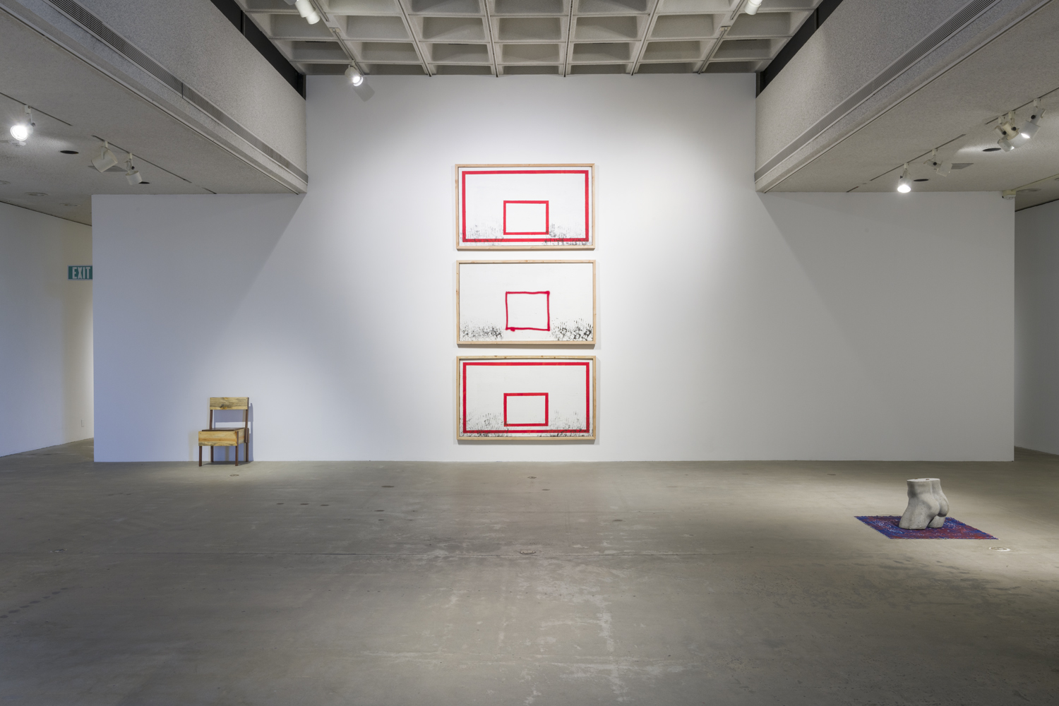 In this artwork installation by the artist David Alekhuogie, one artwork is a wooden sculpture of a low-sitting chair with rectangular, blocky shapes. To the right of this work, are three, vertically hanging artworks that resemble basketball backboards. In these works, there are various numbers of black handprints towards the bottom edge of the artworks. The background for these works is white with red outlines for the frame and rim. To the right of these works is a concrete, naked bust of a male mannequin figure. This artwork is placed on top of another artwork that depicts a blue bandana with red paint splattered on it.