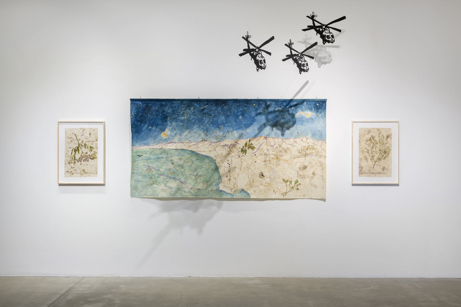 In this artwork installation by the artist Sandy Rodriguez, there are two small framed paintings featuring various plants. In the middle of these two works is a large, horizontal artwork depicting the San Gabriel Mountains. Hanging above this work are three small black helicopter sculptures with skull fronts.