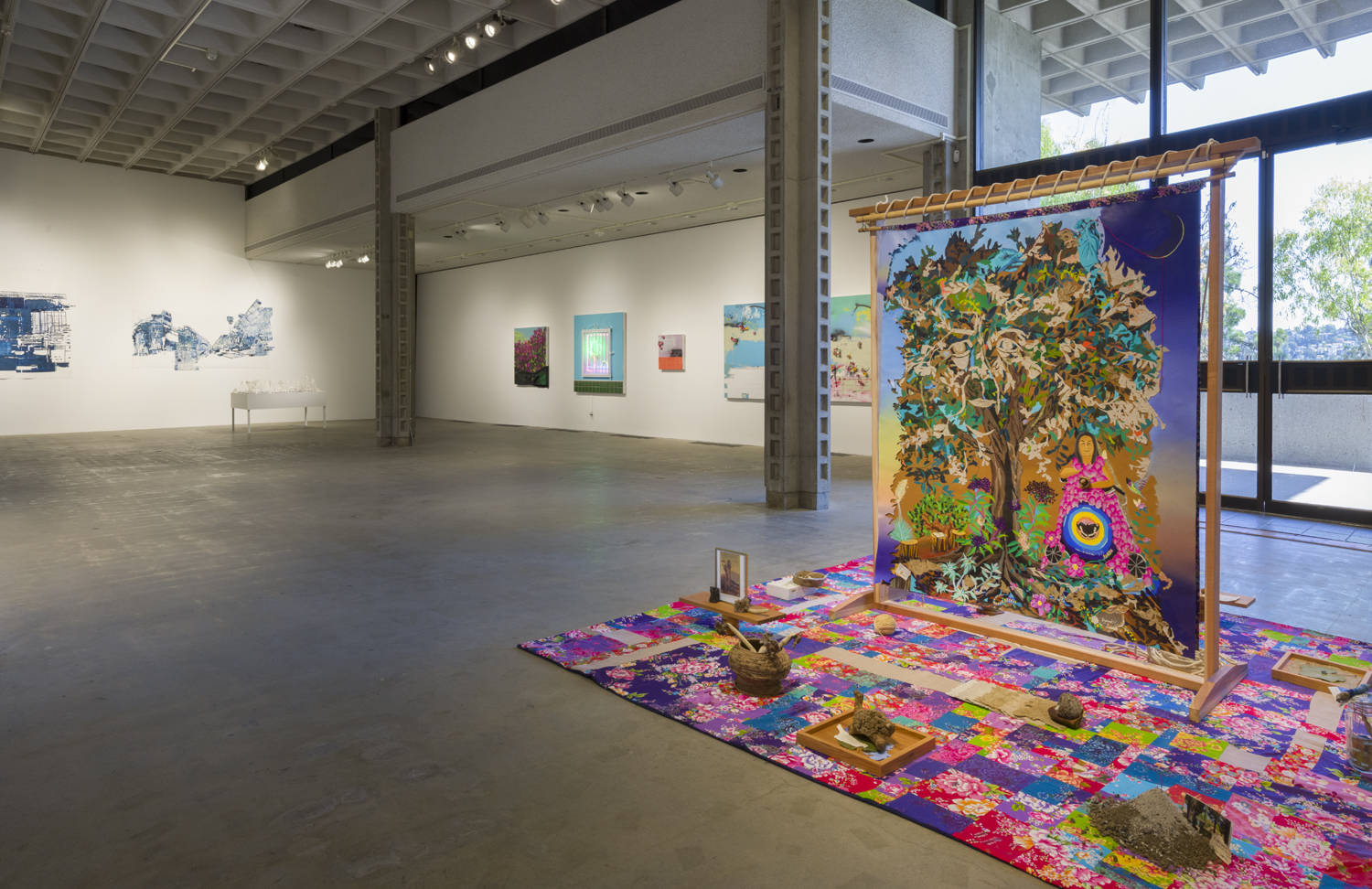 In this art installation, there is one large artwork by the artist iris yirei hu that features a floral textile with pink, purple, blue and yellow colors on the floor. There are also various objects, such as a pile of dirt, a woven basket and a picture frame placed on the textile. Standing in the middle of the textile is a large freestanding tapestry that depicts a woman wearing a bright pink robe and standing next to a tree. To the left of this artwork installation are artworks by the artist Patrick Martinez, including a neon image of a palm tree, a small purple and orange painting, and another painting of bougainvillea. To the left of these artworks is a different artwork installation by the artist Fran Siegel. These artworks include white and blue abstract paperworks hanging on the wall, and a white table with white ceramic, abstract forms sitting on top.