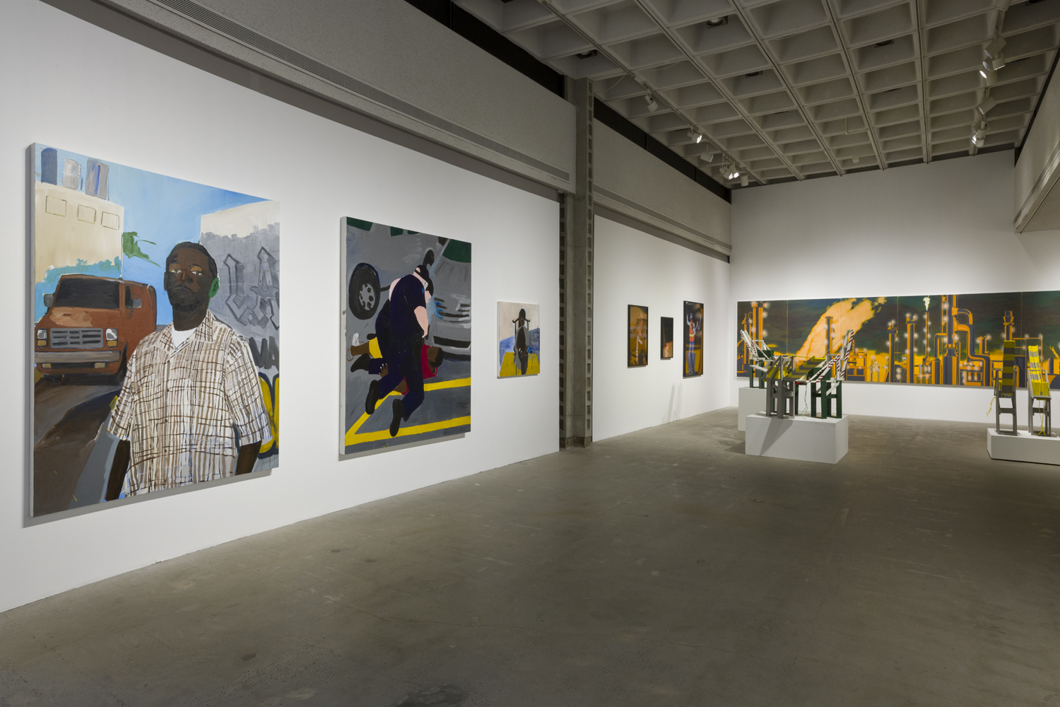 The artwork installation by the artist Henry Taylor features three paintings of various sizes depicting different figures. One painting depicts a male, person of color wearing a light colored checkered shirt with a brown van parked behind him over his left shoulder. To the right of this painting are two figures (a white police officer and a person of color) in a struggle on the floor. To the right of this artwork is a small painting of a male, person of color sitting in a brown chair. To the right of this artwork installation is another installation by a different artist named Mario Ybarra Jr. This artwork installation includes a large, horizontal painting of the cityscape of Wilmington in black and orange colors, photographs of construction workers, and medium-sized wooden replicas of cranes placed on top of white pedestals.