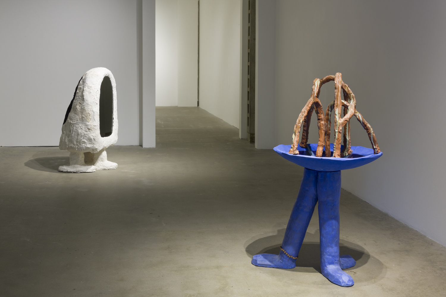 The two artwork sculptures by the artist Anna Sew Hoy depict amorphous figures. One of the figures is blue with three legs with a bird bath on top, and the other figure has two legs and a black mirror front.