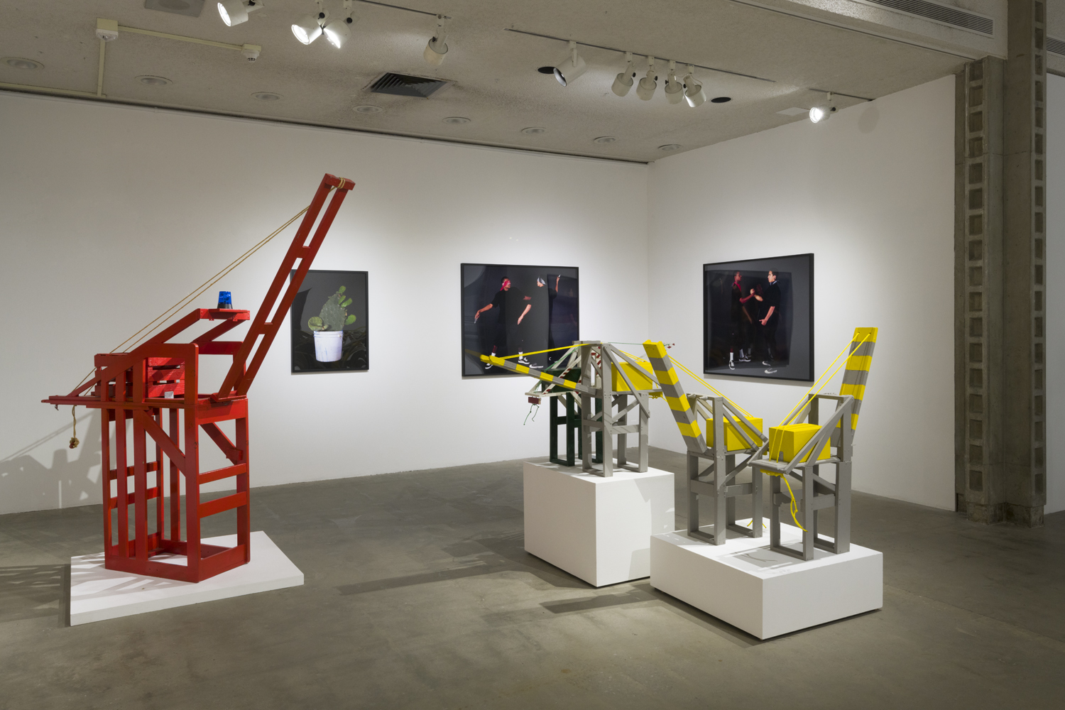 In this artwork installation by the artist Mario Ybarra Jr., there is one large red, wooden sculpture depicting a crane, with two smaller wooden sculptures depicting cranes (painted grey and yellow) to the red crane's right. There are also three photographs hanging on the wall behind these sculptures; one depicts a cactus, another photograph depicts two figures of color engaged in a knife fight, and the other photograph depicts the same two figures clasping hands in a friendly manner.