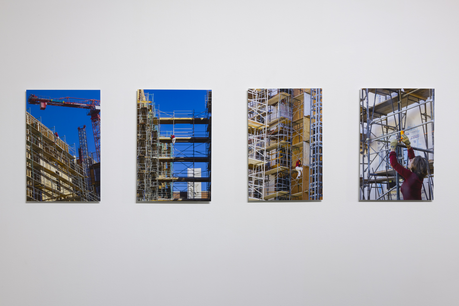In this artwork installation by the artist Nancy Popp, there are four photographs of different construction sites. In each of the photographs, the artist is depicted in the midst of tying orange rope in and around the construction sites.