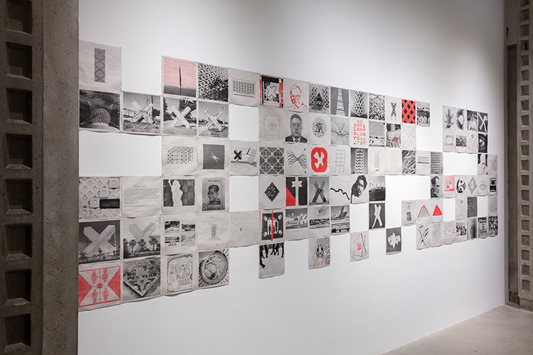 The artwork installation by the artist Ramiro Chaves features several paper drawings and prints displayed in six rows. The papers are white and the images and/or texts printed are a combination of blacks, whites, greys, and red. The printed subjects include buildings, symbols, faces of persons, structures, designs, and text, all featuring some variation of an X.