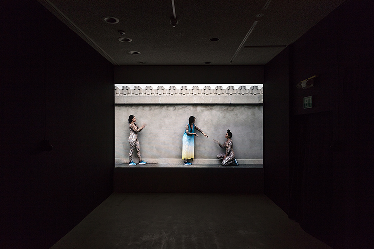 This video installation by the artist Clarissa Tossin presents a tall cement wall with designed etchings along the top portion of the wall located at Hollyhock House. The artwork projects three female perfomers (the same perfomer) at profile view: one (center) dressed in a loose blue-white-yellow gradient dress while the other two on either side are dressed in tan/yellow cheetah print spandex. The left subject postured upright and angled arm gesture, the center subject is postured slanted and downward directed arm gestures, and the right subject knelt down and gestured upwards.