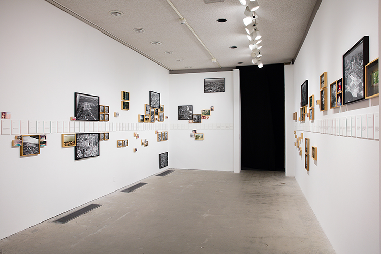 This artwork installation by the artist Jonathas de Andrade includes a variety of small, medium, and large photographs depicting a variety of intimate close-up images and birds-eye-view of cityscapes, as well as reproductions of pages from a diary the artist found. The photoworks are hung in black or brown wooden frames on the walls of a room. The photographs are both in color and black and white and hung at a variety of levels along the walls. The reproductions of the pages from a diary are placed horizontally in the middle between the rows of photographs.