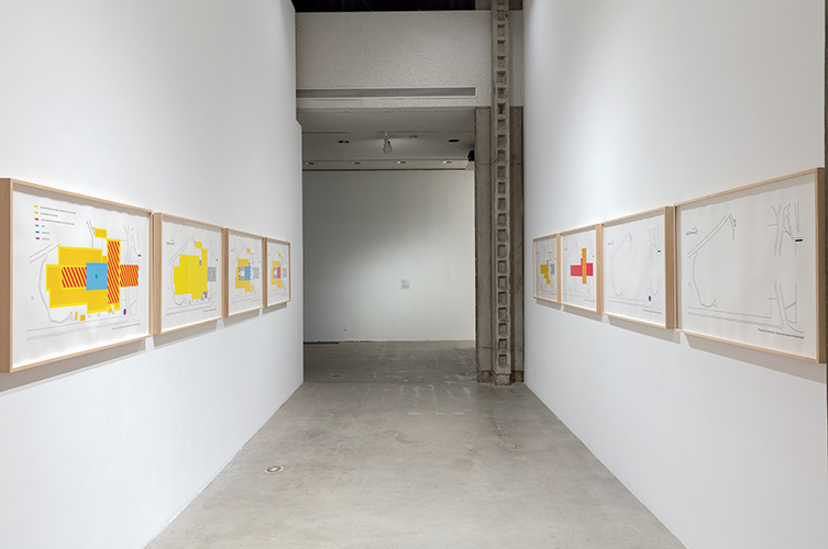 The artwork installation by the artist Eduardo Abaroa includes eight large white prints with color-coded maps and schematics of the propopsed destruction of National Anthropology Museum in Mexico City in blues, reds, yellows, and blacks. Each print is framed in a light brown wooden frame. Four of eight artwork prints are hung side-by-side on two walls facing each other.