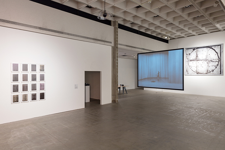 This installation view includes artworks by the artists Manuel Piña, Terence Gower, and Tercerunquinto. The artwork on the left, by Manuel Piña, includes sixteen black and white photos hung, closely together in a grid-like pattern, in white frames. The photographic works present images of large deteriorating buildings and structures. The center artwork, by Terence Gower, includes a black and white video still projected onto a large screen suspended from the ceiling of the gallery. The video still presents a large stage setting whith an individual, dressed in black, at the center; back turned and gesturing upward. The arwork on the right, by Tercerunquinto, includes a large scale black and white rectangular frame and image made up of six panels producing a grid-like pattern with an additional circular distinction in the center of the artwork. The image represents empty place where the seal of Mexico was placed at the Centro Cultural Universitario Tlatelolco in Mexico City.