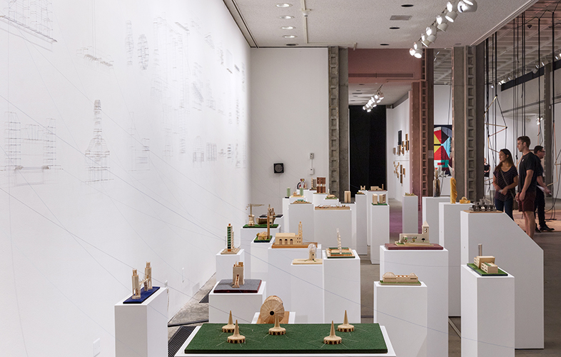 This artwork installation by the artist Carlos Garaicoa includes several small, wooden architectural models of a variety of buildings and structures (both real and fictional) from Cuba set on various colored mats on top of white pedestals. Each architectural model has a thread that connects it to the wall behind these models; these connecting threads and pins re-create the archictural models as drawings on the wall.