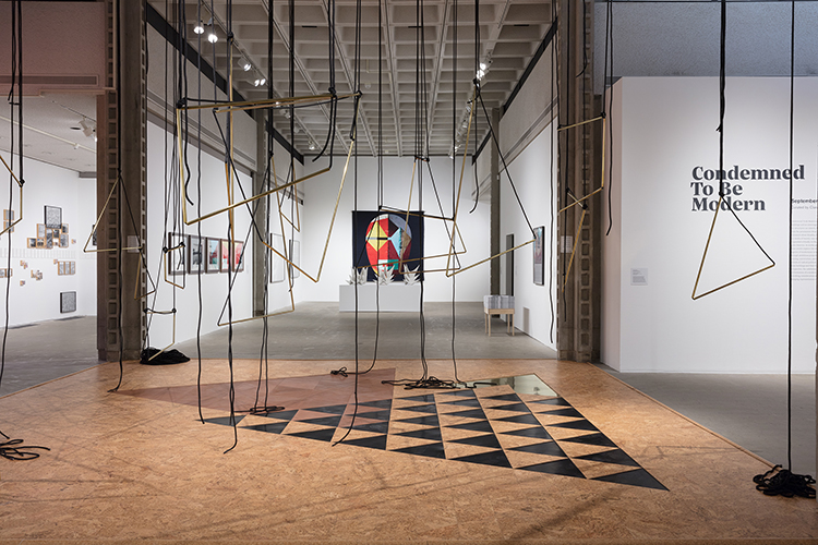 This installation view of the Condemned To Be Modern exhibition includes artworks by Lenor Antunes, Jonathas de Andrade, Mauro Restiffe, Héctor Zamora, Alexandre Arrechea, and Lais Myrrah. In the foreground, the artwork by Lenor Antunes features geometric, copper scultpures suspended from the gallery ceiling by black rope. In the background, the left-most artwork by Jonathas de Andrade includes clusters of square framed images hung onto white walls. The artwork on the inner left wall by Mauro Restiffe includes seven black and white photographs hung in black frames horizontally along a wall. The images includes bodies of water, and linear architectural buildings and structures. In the center background, the artwork by Héctor Zamora includes a large cubic plynth/pedestal base upholding nine triangularly geometric concrete forms. Further in the background, the artwork by Alexandre Arrechea includes a mask-like render produced by basic geometric shapes of varying colors: red, yellow, cyan, and brown onto a large black surface. In the background, the right-most artwork by Lais Myrrah includes a small light brown wooden table/stand upholding a large quantity of square posters. The artwork also includes a medium-sized color poster with a blue toned image and black text within a black frame hung on the wall.